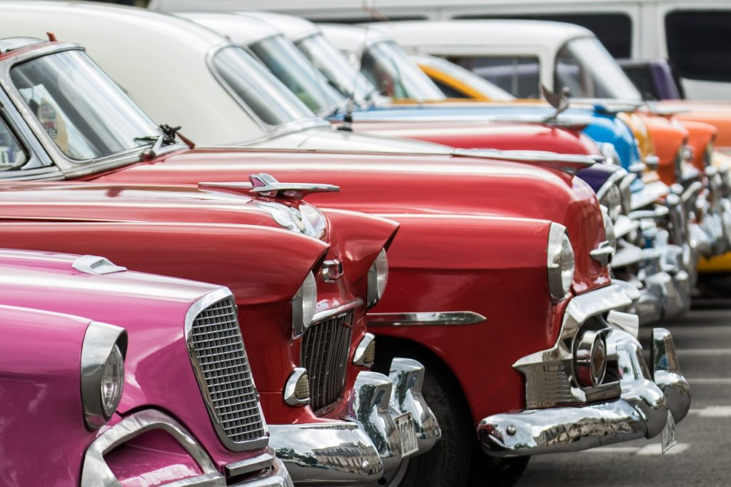 Image of pink, red and blue vintage American cars lined up on the streets of Cuba
